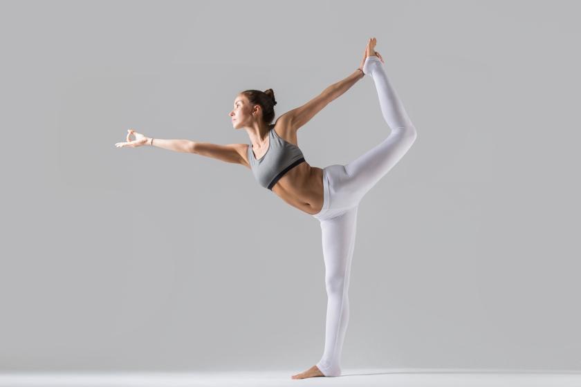 Young woman in Natarajasana pose, grey studio background