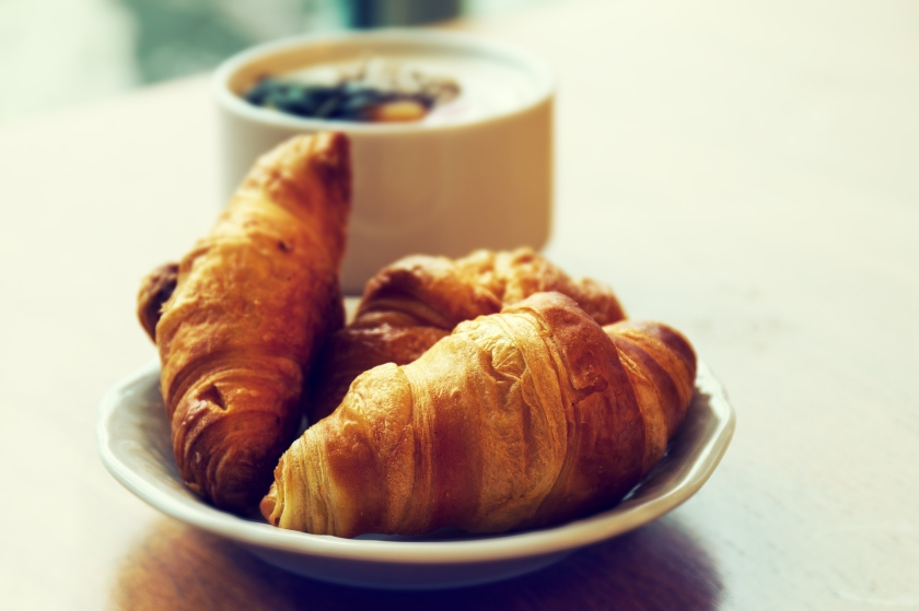 Tasty fresh breakfast with croissants on plate on wooden table.